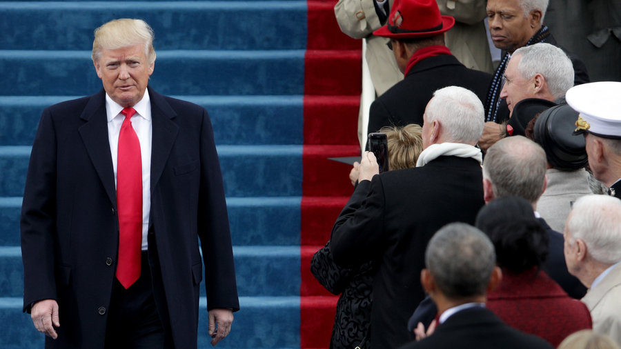 Trump on inauguration day Jan 20, 2017 wearing a dark overcoat and a red shiny satin tie that extends way past beyond the waistband pointing at his crotch - not very flattering