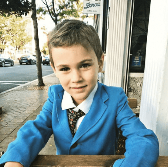 Emmett wearing a bright blue jacket and tie with a geometric print that is appropriate to his age.