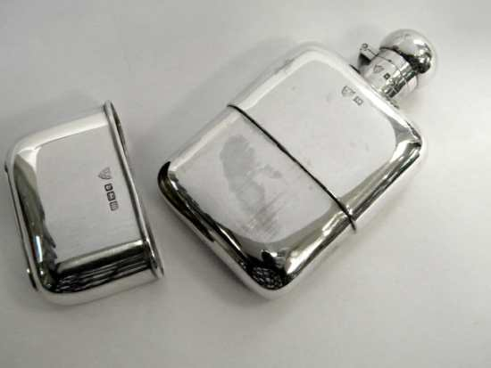 A vintage silver hip flask with a detachable bottom