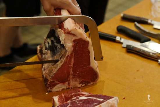 T-bone steak being cut by hand