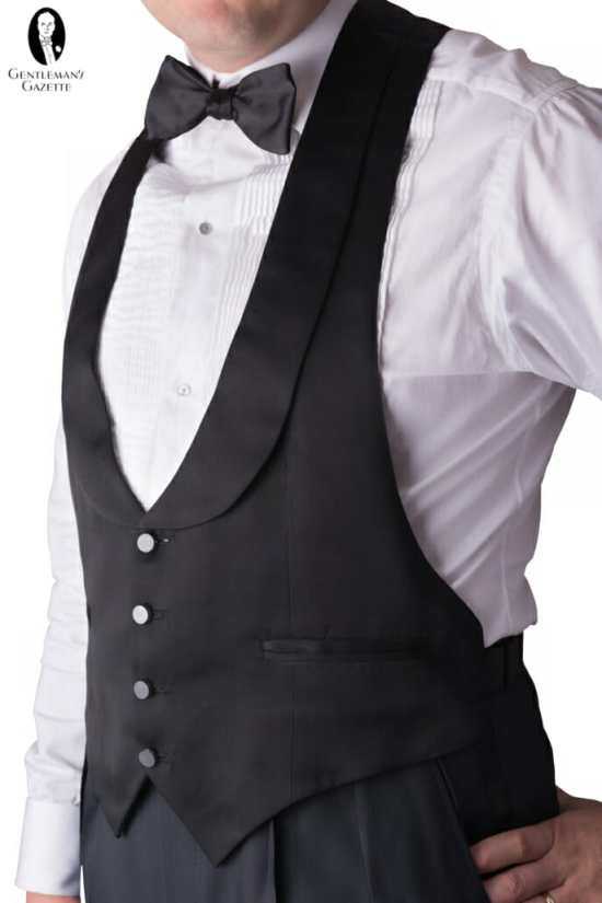 This black-tie waistcoat is a backless model, and features four polished buttons, a matte wool body with self-faced lapels, and two jetted pockets.