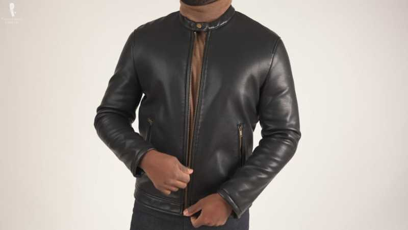 Kyle trying to zip a black leather jacket that's already too small for him.