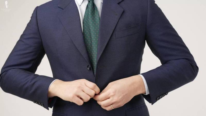 Raphael buttoning a tight navy suit