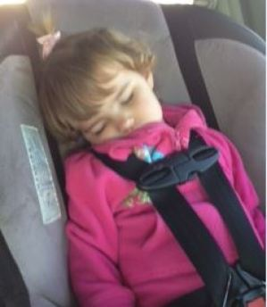 toddler sleeping wearing seat belt in booster seat