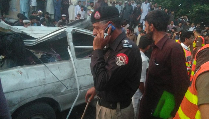 Police officials pictured beside the crushed passenger van at the site of the accident in Abbottabad. Photo: Geo News