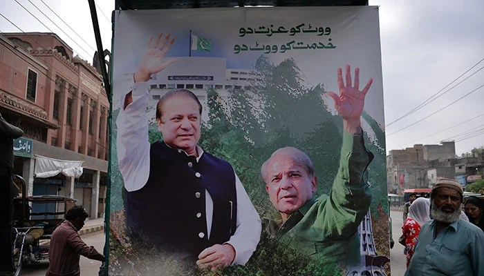 Supporters of former prime minister Nawaz Sharif stand beside a poster featuring Nawaz Sharif (L) and his younger brother Shehbaz Sharif at the venue where Shahbaz will lead a rally towards the airport ahead of the arrival of Nawaz from London, in Lahore on July 13, 2018. Photo: AFP