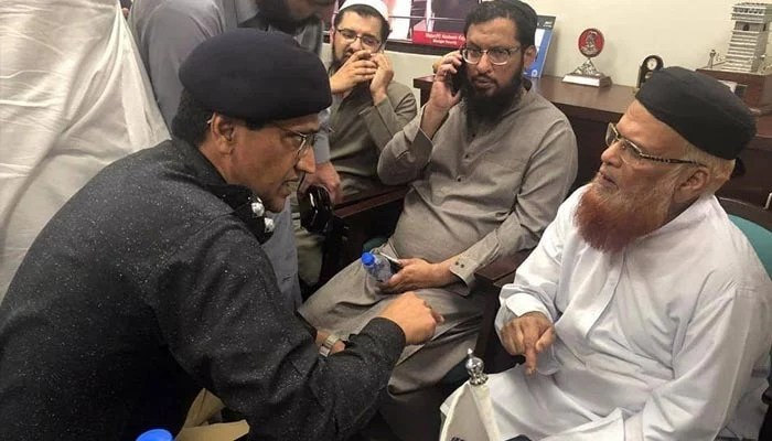 Moulana Taqi Usmani speaking to a police official after his car was attacked in Karachi