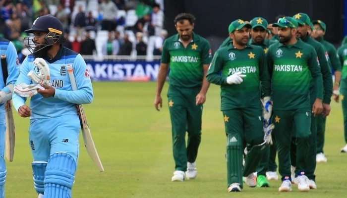 Pakistan, England cricket team members walk off the pitch after the match ends. Photo: AFP