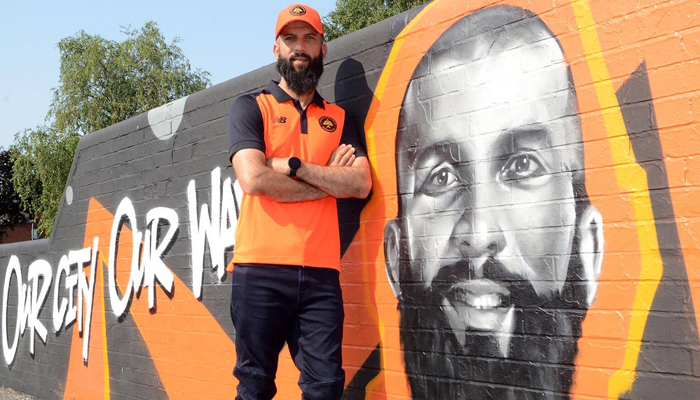England cricketer Moeen Ali stands beside his mural painted at Spark Green park in Birmingham. — Photo by author