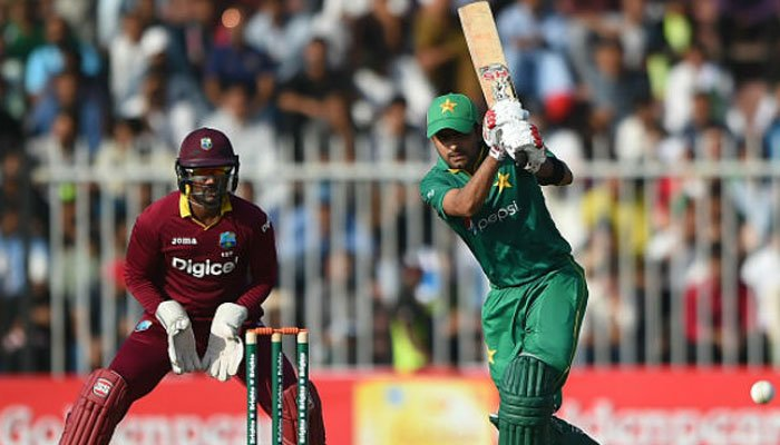 A Pakistani batsman playing a shot while West Indian wicketkeeper looks on