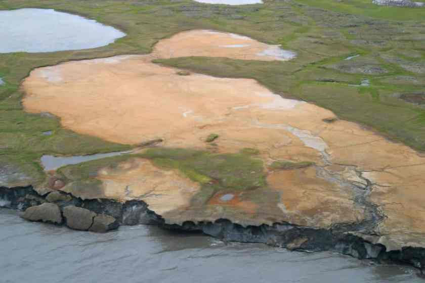 An oblique aerial photograph of Flaxman Island off the Alaska coast.   A tapped thermokarst lakes, caribou tracks, and ice-rich bluffs that are eroding can be observed in this photo.  Photo: Bruce Richmond/Ann Gibbs, USGS. Public domain.