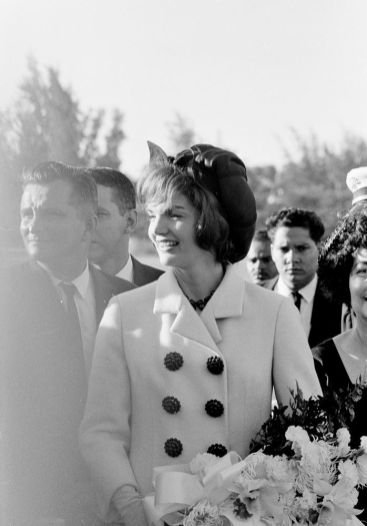 """First Lady Jacqueline Kennedy upon her arrival at Isla Verde International Airport in San Juan, Puerto Rico. First Lady of Puerto Rico, Inés Mendoza, stands on far right edge of image."""