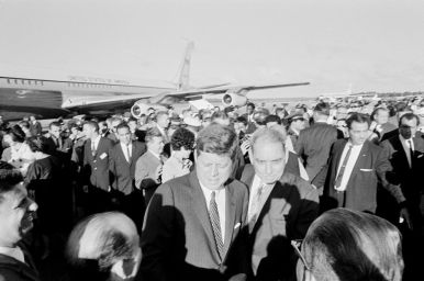 """President John F. Kennedy and Governor of Puerto Rico Luis Muñoz Marín (right) visit with those gathered at Isla Verde International Airport to welcome President Kennedy upon his arrival. San Juan, Puerto Rico."""