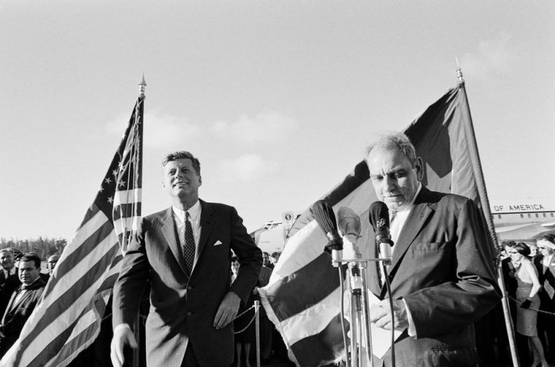 """President John F. Kennedy stands with Governor of Puerto Rico Luis Muñoz Marín (right) upon the president's arrival at Isla Verde International Airport, Puerto Rico."""