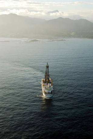 "After the March 2011 Mw 9.0 Tohoku-oki Earthquake, the Deep-sea Drilling Vessel (D/V) Chikyu, seen here off-shore Japan, installed a sub-seafloor temperature observatory through the plate boundary fault as part of the Integrated Ocean Drilling Programs' Japan Trench Fast Drilling Project. Fulton and Brodsky present analysis of the observatory data to reveal signals interpreted to be the thermal signature of pulses of water squirting out of fractures in response to aftershocks on neighboring faults. The observation of interactions between faults during the aftermath of a major earthquake helps scientists gain a better understanding of the processes that control earthquake occurrence. See the open-access article, ""In situ observations of earthquake-driven fluid pulses within the Japan Trench plate boundary fault zone,"" by Fulton and Brodsky. Click on the image for a larger version. Photo Credit: JAMSTEC/IODP."