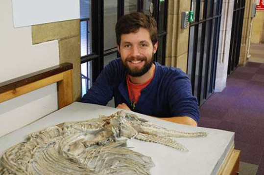 Jonathan Hanson with the ichthyosaur skeleton at the School of Earth Sciences. Credit: University of Bristol