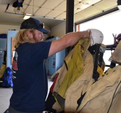 Smokejumpers hang their jumpsuit gear on speed racks in the ready room so they can quickly suit up for fire deployment.