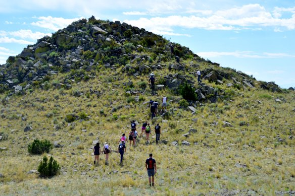 "Webb School students hiking up to the ""Looking-Out"" site associated with the buffalo jump. A eagle catchment area is immediately below the highest point of the ""Looking-Out"" site."
