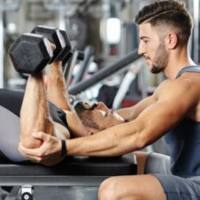 35068077 - personal fitness trainer helping a man at a chest workout with heavy dumbbells