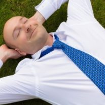 14282747 - businessman in shirt and tie relaxing on grass looking happy