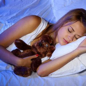 21529778 - young beautiful woman with toy bear sleeping on bed in bedroom