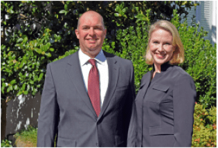 Man in suit and woman in black shirt stand in front of large green foliage