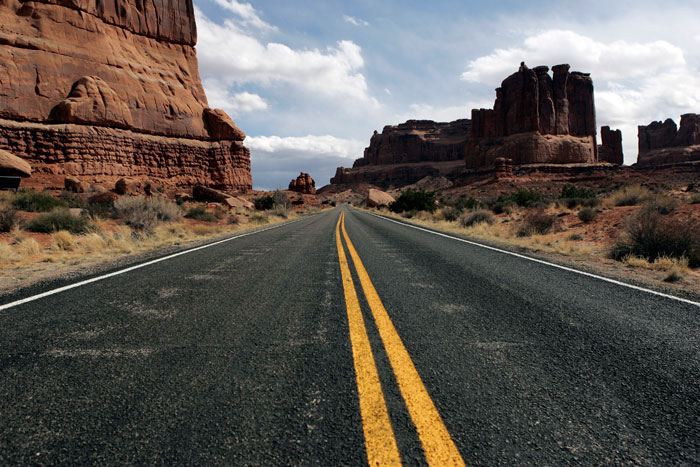 Canon EOS 1D MarkII — 24mm ISO 100 @ f/5.6 and 1/250 sec — The roadway carves through the landscape at Arches National Park just outside of Moab, Utah.