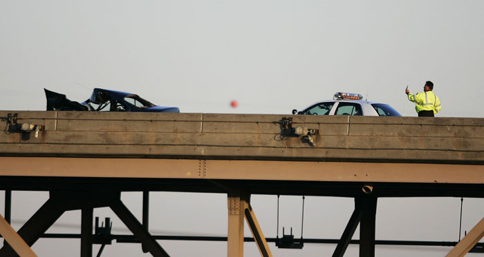 Friday, December 5, 2008 A police officer holds up his cell phone at the scene on an early-morning fatal accident that blocked all traffic on the Martin Luther King bridge.  Max Gersh   Post-Dispatch ©2008