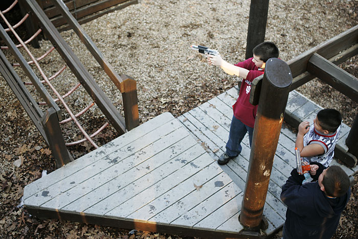 A kid takes aim and fires his airsoft pistol in the Baker Park playground. (C-T photo Max Gersh) ©2010