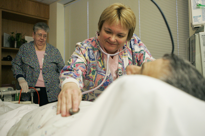 Anita Reinhart listens to the heart and lungs of a patient Wednesday evening in the Progressive Care Unit at Henry County Hospital. Dianne Stephens, left, assisted Reinhart with an IV change. (C-T photo Max Gersh) ©2010