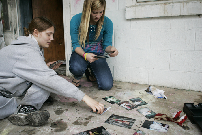 Juliana, left, and Brooke Hughes sort through salvaged photographs Wednesday afternoon. A fire broke out Wednesday morning in their shared closet while they were at school. (C-T photo Max Gersh) ©2010