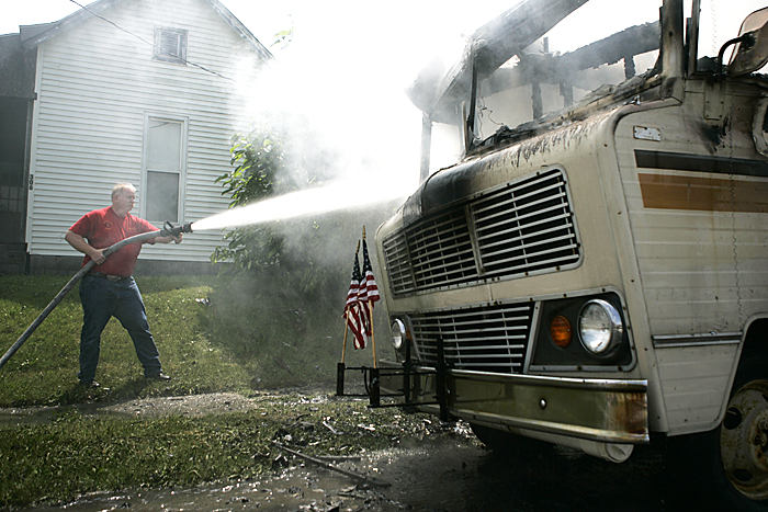 New Lisbon firefighter Eric Keesling finishes extinguishing a Winnebago that burst into flames Monday shortly after the Memorial Day parade in New Castle. Keesling and other members of the New Lisbon Fire Department were headed home when they saw the RV on fire. (C-T photo Max Gersh) ©2010