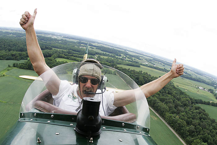 Ted Davis lets go of the stick on his 1937 New Standard D-25 biplane Tuesday afternoon during the Hagerstown Flying Circus. Davis was piloting 15-minute plane rides for $60 per person. (C-T photo Max Gersh) ©2010