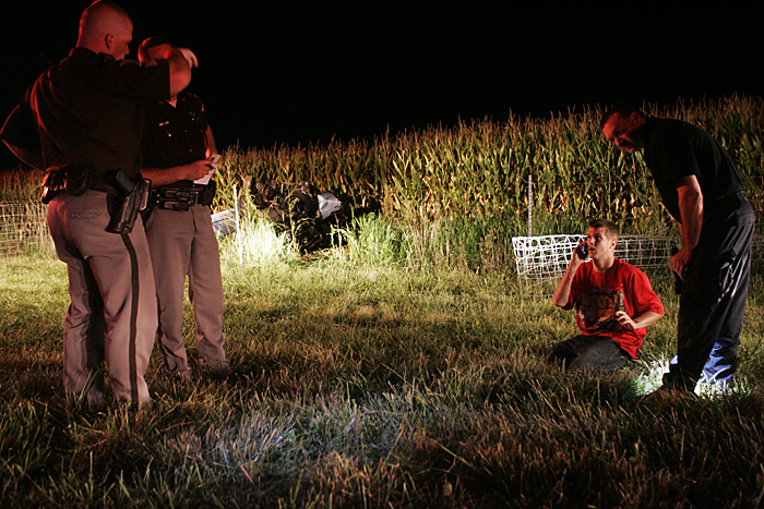 Justin Ryan Pierce, 19, of Mount Summit, talks on his cell phone late Wednesday night after crashing a 1987 Mercedes Benz in a confield near the intersection of Road 300S and Ind. 103. His passenger, Jimmy Luna, 17, New Castle, was flown from the scene to Methodist Hospital in Indianapolis. (C-T photo Max Gersh) ©2010