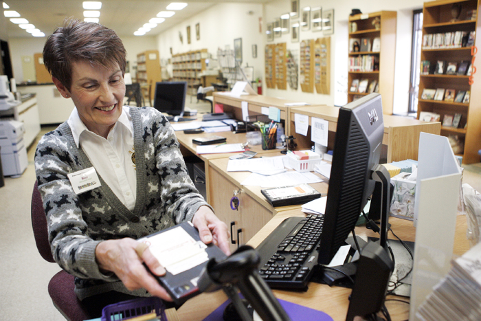 MAX GERSH | ROCKFORD REGISTER STAR Library clerk Kay Kluth scans in a DVD Tuesday, March 1, 2011, at the front counter of the Pecatonica Library. ©2011