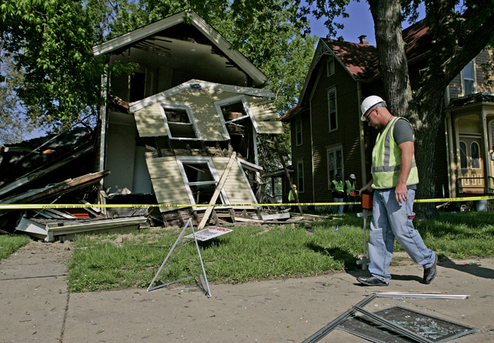 MAX GERSH | ROCKFORD REGISTER STAR A Nicor employee surveys the scene of a house explosion in the 400 block of Kishwaukee St. Friday, May 20, 2011, in Rockford. ©2011