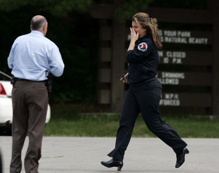 MAX GERSH   ROCKFORD REGISTER STAR Winnebago County dispatcher Tracy Wilson runs from her vehicle into a waiting police car after her 17-year-old son, Mitchel Krause, was pulled from the water Tuesday, June 14, 2011, at a boat dock in Rock Cut State Park in Loves Park, Ill. ©2011