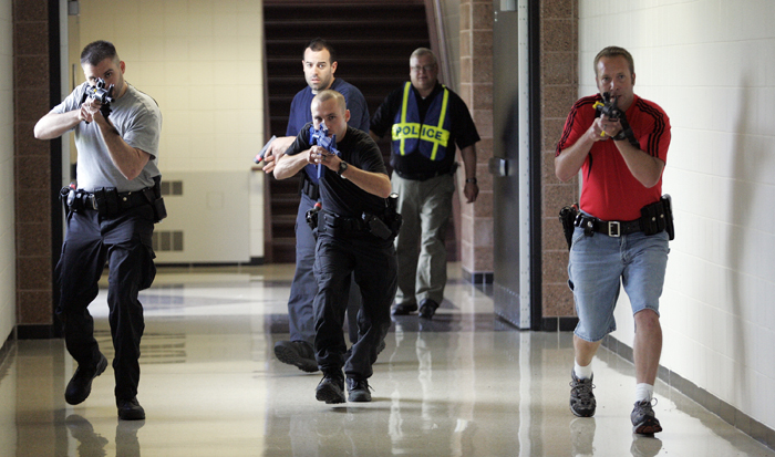 MAX GERSH | ROCKFORD REGISTER STAR Cherry Valley Police Chief Todd Houde (back right) watches as Clint Wagner (from left) of the Rockford Police Department, Jason Hergenroeder of the U.S. Marshals Service (rear center), Robert Lewis of the Roscoe Police Department and Ryan Fulton of the Cherry Valley Police Department make their way down a hall Wednesday, Aug. 10, 2011, during rapid deployment to an active shooter training at Harlem High School in Machesney Park. ©2011