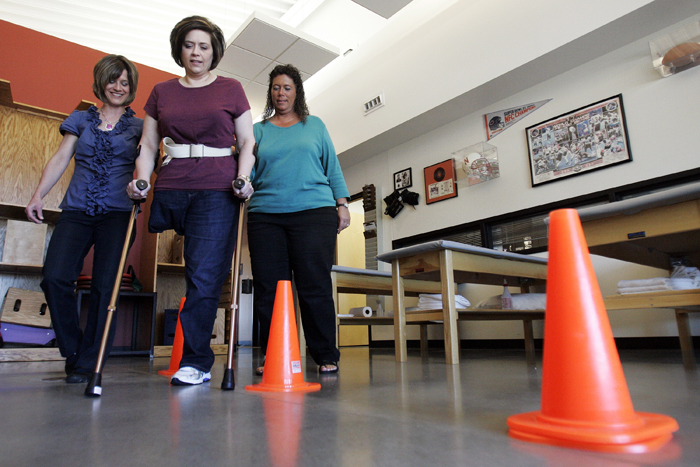 "MAX GERSH | ROCKFORD REGISTER STAR Physical therapist Alane Curry (left) and physical therapy technician Betty Kendell (right) walk alongside Colleen Mains of Loves Park while she practices using forearm crutches Wednesday, Oct. 5, 2011, at Orthopedic Rehab Specialists in Rockford. Mains lost her right leg when bone cancer developed on the right side of her pelvis. ""It was literally a life over limb decision,"" Mains said. © 2011"