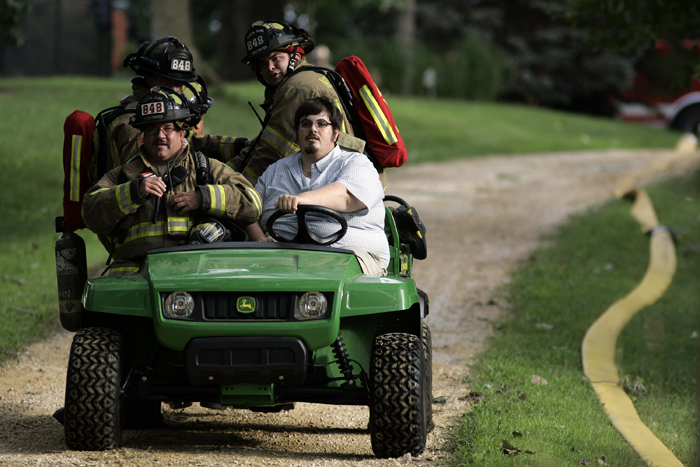 MAX GERSH   ROCKFORD REGISTER STAR Tyler White of Sharon, Wis., shuttles firefighters from Auburn Street down a dirt road to a home on fire Friday, July 29, 2011, in Winnebago. White, whose family's home neighbors the one on fire, was in town helping his family clean up storm damage. ©2011