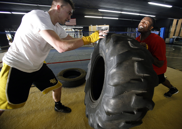 """Ryan Newman (left), 20, and Joshua Patterson, 24, push a tire back and forth during a """"standing pushup"""" exercise Tuesday, April 30, 2013, at Fight College on North Main Street in Rockford. MAX GERSH/ROCKFORD REGISTER STAR ©2013"""