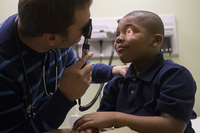 Dr. Thomas Danko looks at OmarLe'quan Stearns' eyes Wednesday, March 5, 2014, during his six-year exam at Crusader Community Health in Rockford. MAX GERSH/RRSTAR.COM ©2014
