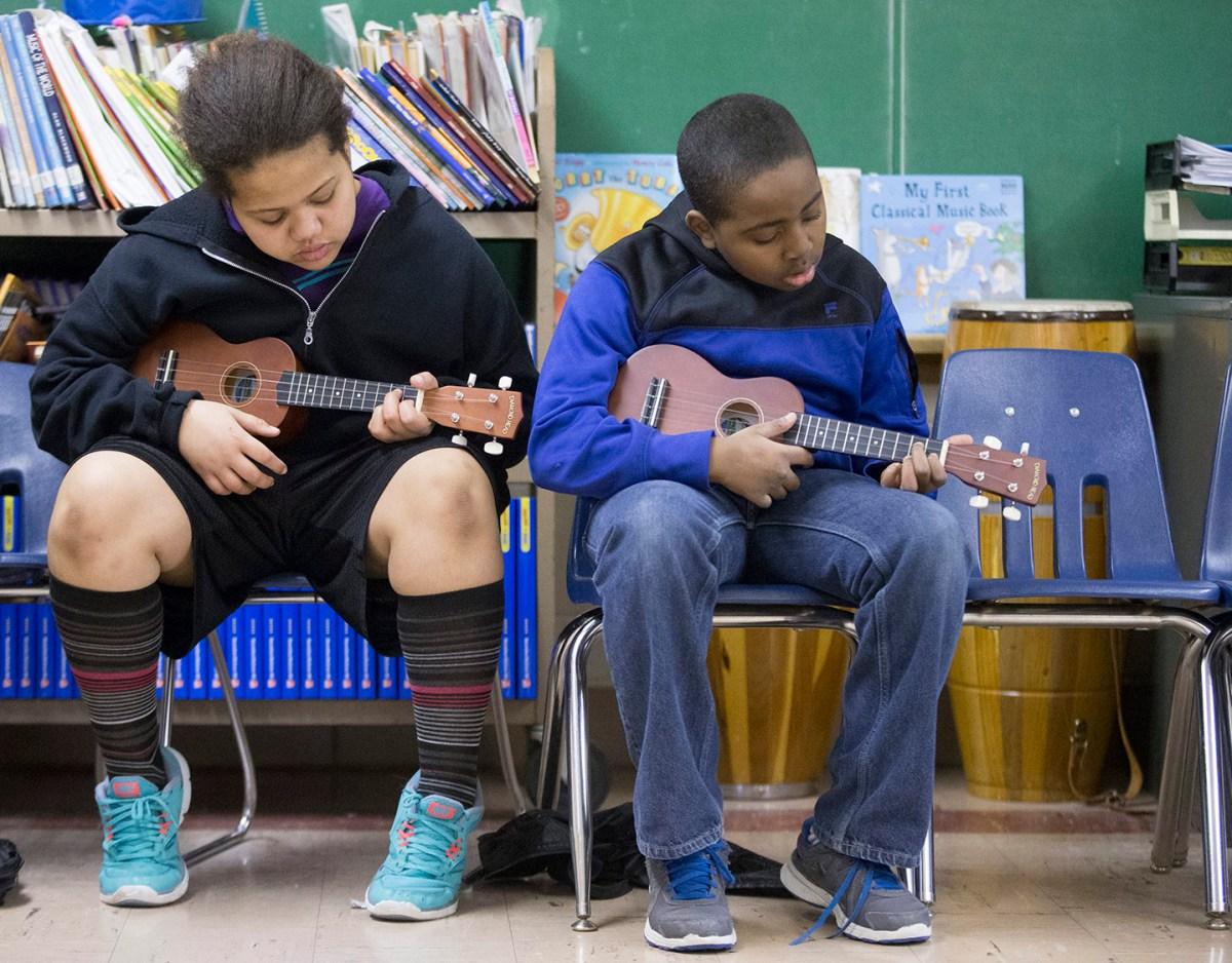 Students play the ukulele