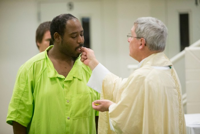 Cornelius Brooks receives communion from Bishop David J. Malloy on Sunday, March 27, 2016, during Easter Mass at the Winnebago County Jail in Rockford. MAX GERSH/STAFF PHOTOGRAPHER/RRSTAR.COM ©2016