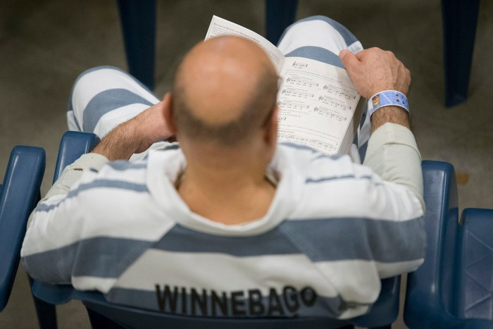 An inmate follows along with the service Sunday, March 27, 2016, during Easter Mass at the Winnebago County Jail in Rockford. MAX GERSH/STAFF PHOTOGRAPHER/RRSTAR.COM ©2016