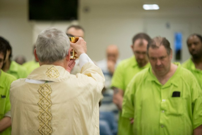 Bishop David J. Malloy holds up a chalice Sunday, March 27, 2016, during Easter Mass at the Winnebago County Jail in Rockford. MAX GERSH/STAFF PHOTOGRAPHER/RRSTAR.COM ©2016