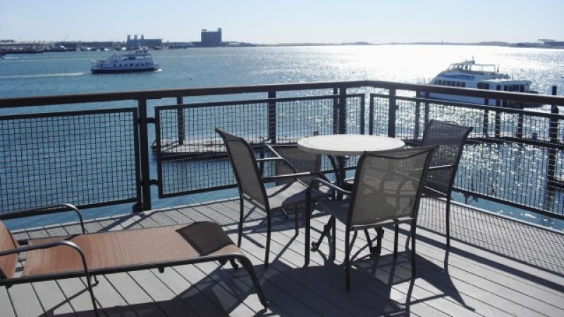 Large outdoor deck overlooking Boston Harbor with ferries in background, Private Deck at Boston Yacht Haven Inn and Marina, Boston, MA