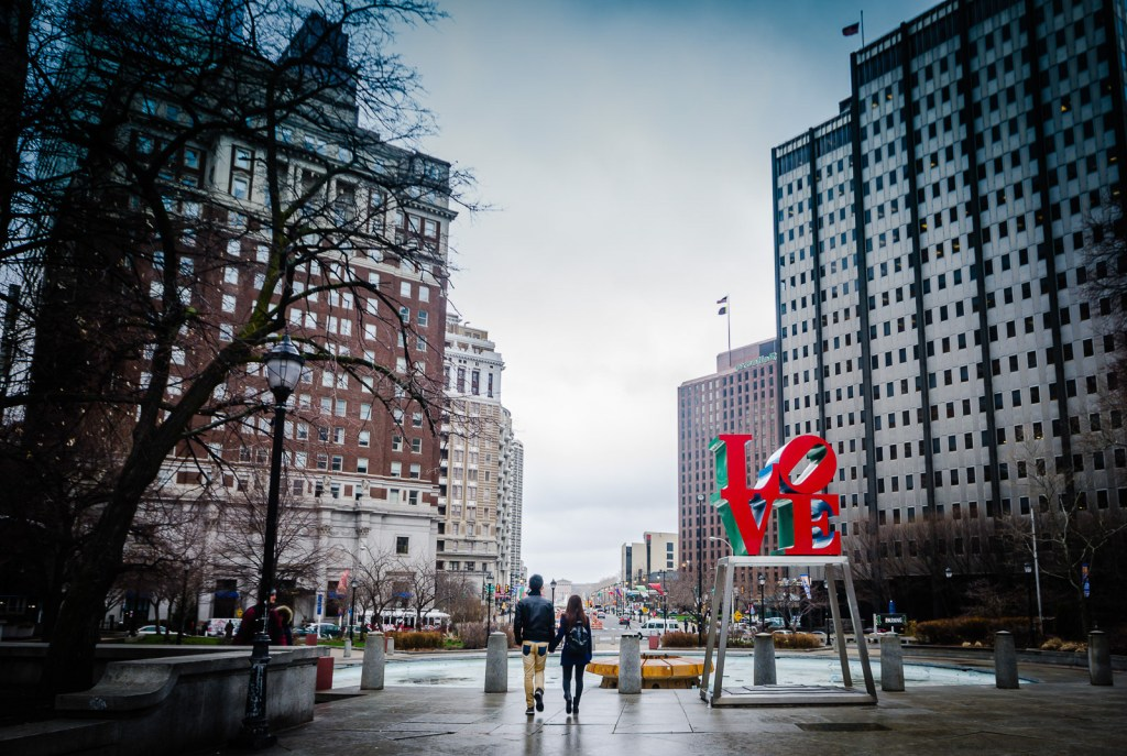Couple walks holding hands past the Philadelphia Love Sign.