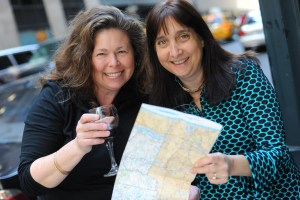 The Getaway Mavens, Sandra Foyt and Malerie Yolen-Cohen, holding map and wine glass.