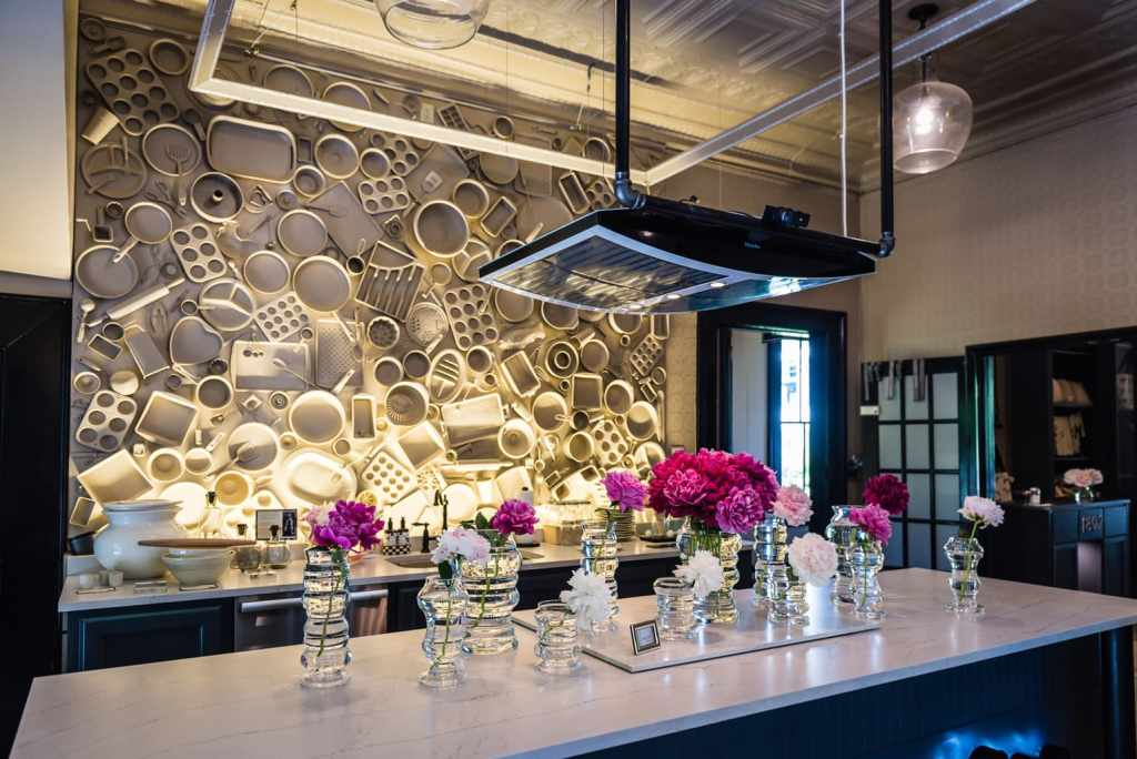 Show kitchen counter backed by Wall of Neighbors Art Installation at Beekman 1802 Home Wares Shop in Sharon Springs NY.